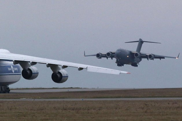 A British C17 transport plane lands next to a Russian Antonov which was hired by the French army to transport equipment to Mali, at the army base in Evreux, 90 kms(56 mls)north of Paris, Monday, Jan.