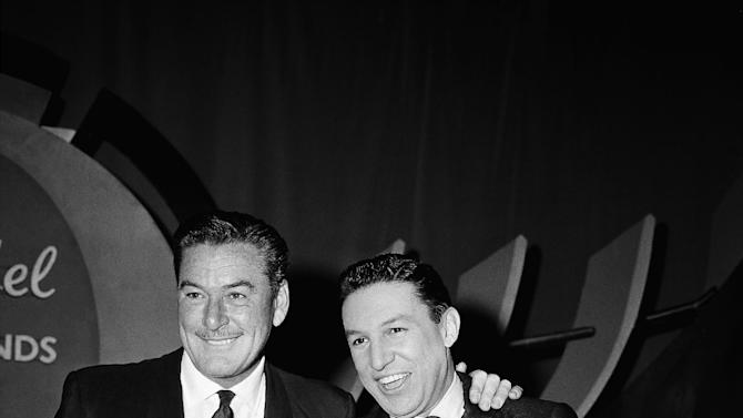 """FILE - In this Feb. 12, 1957 file photo, actor Errol Flynn, left, and television host Mike Wallace are shown before NBC's """"The Big Surprise"""" TV quiz show, in New York. The quiz show is hosted by Mike Wallace. Wallace, the dogged, merciless reporter and interviewer who took on politicians, celebrities and other public figures in a 60-year career highlighted by the on-air confrontations that helped make """"60 Minutes"""" the most successful primetime television news program ever, has died. He was 93. (AP Photo/Matty Zimmerman, File)"""