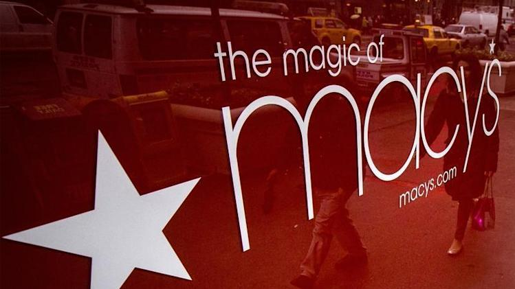 People are reflected in a window outside Macy's department store in New York
