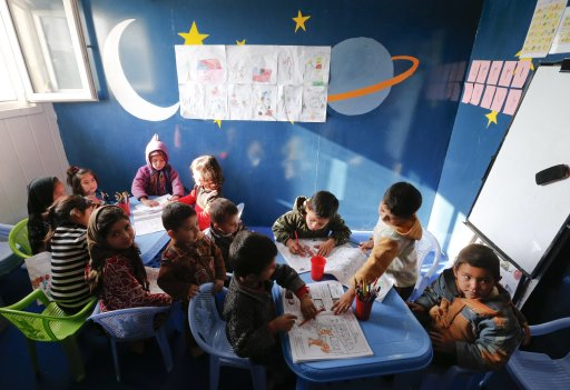 Children play with their colouring books at a kindergarten for female Afghan National Police (ANP) officers and Afghan staff at a training centre near the German Bundeswehr army camp Marmal
