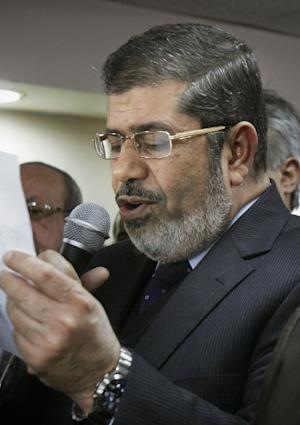 FILE - In this Monday, Jan. 16, 2012 file photo, Mohammed Morsi speaks at a press conference in Cairo, Egypt. The leader of Egypt's largest Islamist party says U.S. threats to cut aid over a spat about nonprofit groups operating in the country are out of line and could imperil the peace deal with Israel. Mohammed Morsi, the leader of the political arm of the Muslim Brotherhood, Freedom and Justice Party, said the hundreds of millions of dollars Egypt gets every year from the U.S. are part of its commitment to the 1979 peace deal with Israel. (AP Photo/Mohammed Abu Zaid, File)