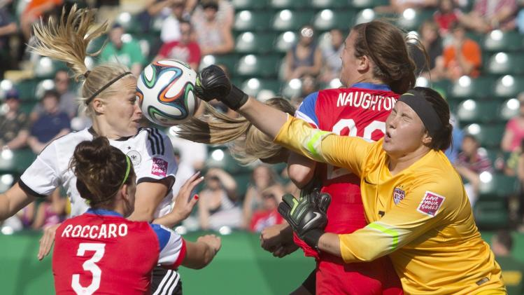 USA goalkeeper Katelyn Rowland (1) makes the save on Germany's Pauline Bremer as Cari Roccaro (3) and Katie Naughton (20) defend during the first half of a FIFA U-20 women's World Cup soccer match Tuesday, Aug. 5, 2014, in Edmonton, Alberta. (AP Photo/The Canadian Press, Jason Franson)