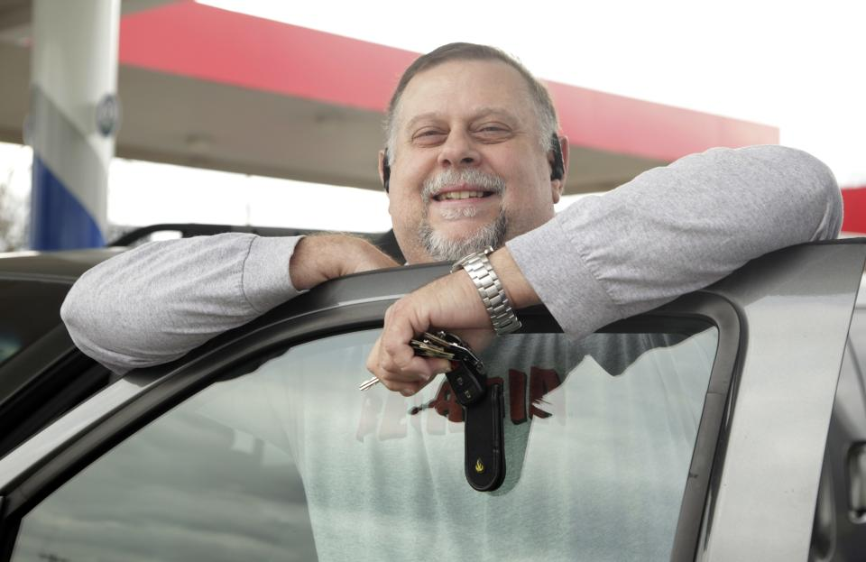 In this Dec. 15, 2011 photo, Michael Reed poses by his car at a gas station in Charlotte, N.C. The retail price of gasoline averaged more than $3.50 per gallon for the year, a record. Drivers cut back where they could, driving less and switching to more fuel efficient cars.(AP Photo/Chuck Burton)