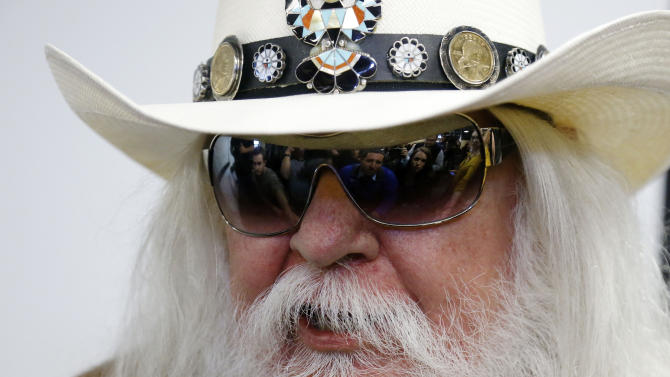 Reporters are reflected in the sunglasses of Leon Russell as he answers a question at a news conference in Tulsa, Okla., Tuesday, Jan. 29, 2013. The Oklahoma Historical Society has acquired a large collection of works by the legendary musician and native Oklahoman that are intended for display in a planned pop culture museum in Tulsa. (AP Photo/Sue Ogrocki)