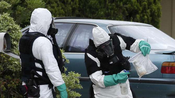 An investigator sprays on a bag containing a bottle collected from a home in Costa Mesa, Calif., Monday, April 15, 2013. A man was blown up in the home  Sunday evening and at least 16 neighbors were evacuated as authorities found and destroyed other explosive devices, police said Monday. (AP Photo/Jae C. Hong)