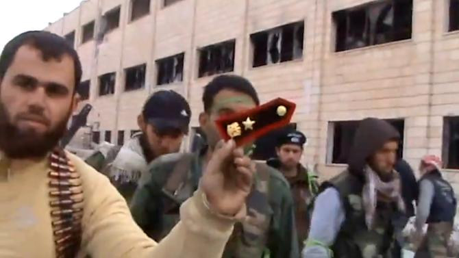 In this Sunday March 3, 2013 image taken from video obtained from the Shaam News Network, which has been authenticated based on its contents and other AP reporting, a Syrian rebel fighters displays an epaulette from a government soldier during a tour of the police academy complex in Khan al-Asal, in the province of Aleppo, Syria. The Britain-based Syrian Observatory for Human Rights said the rebels seized the police academy in Khan al-Asal after entering the sprawling government complex with captured tanks. The Observatory said the battle left at least 120 soldiers and 80 rebels dead. (AP Photo/Shaam News Network via AP video)