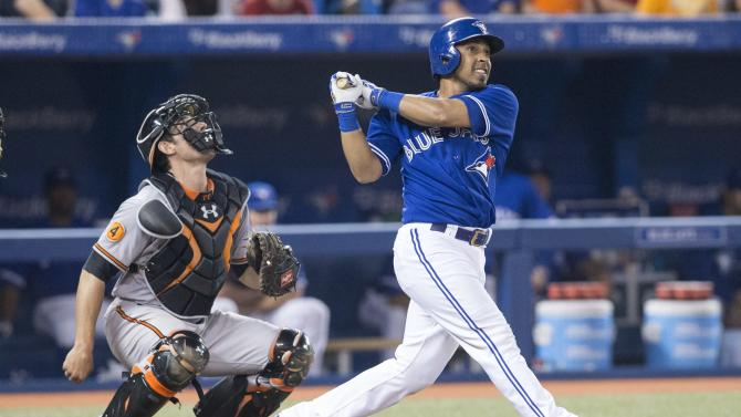 Toronto Blue Jays' Maicer Izturis, right, hits a home run as Baltimore Orioles catcher Taylor Teagarden watches during the fifth inning of a baseball game in Toronto, Saturday, June 22, 2013. (AP Photo/The Canadian Press, Chris Young)