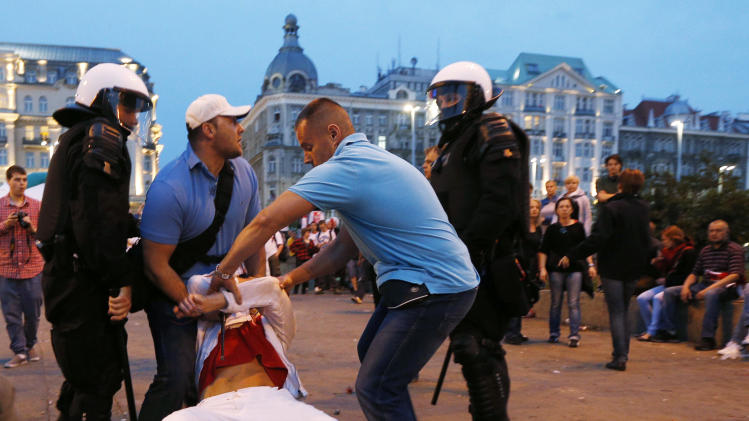Plainclothed police detain a Polish fan during the Euro 2012 soccer championship group a match between Poland and Russia in downtown Warsaw, Poland , Tuesday, June 12, 2012. (AP Photo/Czarek Sokolowski)