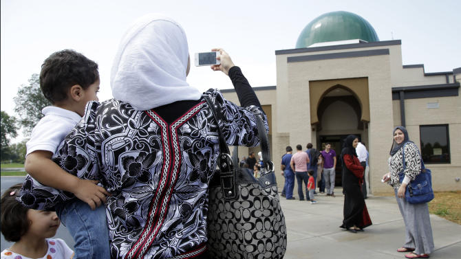 A woman takes a picture of the Islamic Center of Murfreesboro after midday prayers on Friday, Aug. 10, 2012, in Murfreesboro, Tenn. Opponents of  the mosque waged a two-year court battle trying to keep it from opening. (AP Photo/Mark Humphrey)