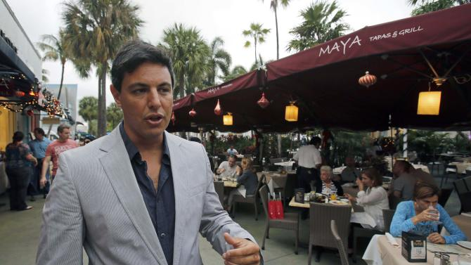 "Alejandro Maya, owner of Maya and Tapas Grill, talks to a reporter at his restaurant in Miami Beach, Fla., Thursday, Dec. 13, 2012. ""Eat in Miami, pay in pesos!"" the ad for the Maya Tapas & Grill restaurant proclaims. At the Maya restaurant along Miami Beach's famed Lincoln Road, clients can pay in Argentine pesos at the official exchange rate. (AP Photo/Alan Diaz)"