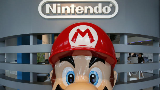 FILE - In this Wednesday, July 31, 2013, file photo, a Super Mario figure greets visitors as children play at Nintendo showroom in Tokyo. Nintendo reports quarterly earnings on Wednesday, Oct. 30, 2013. (AP Photo/Shizuo Kambayashi, File)
