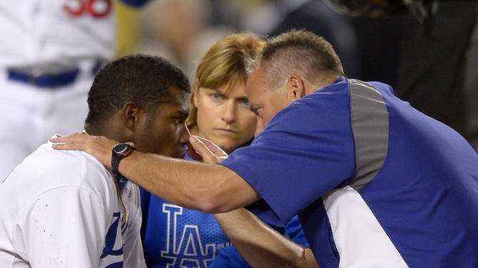 Los Angeles Dodgers' Yasiel Puig, left, is seen to by trainers after being grazed by a pitch during the sixth inning of their baseball game against the Arizona Diamondbacks, Tuesday, June 11, 2013, in Los Angeles.  (AP Photo/Mark J. Terrill)