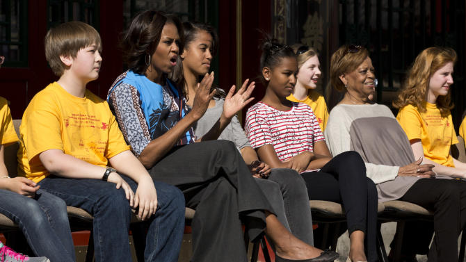U.S. first lady Michelle Obama, second from left, applauds as she and her daughters Malia, third from left, Sasha, fourth from left, and her mother Marian Robinson, second from right, watch a Peking opera performance with a group of American schoolchildren who are visiting China during their spring break, at the Summer Palace in Beijing, Saturday, March 22, 2014. (AP Photo/Alexander F. Yuan)