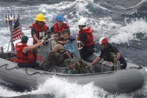 Sailors assist in the rescue of a family with a sick infant via the ship's small boat as part of a joint U.S. Navy, Coast Guard and California Air National Guard rescue effort