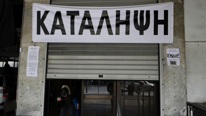 "A man ducks under half-closed shutters, below a sign reading ""Occupied,"" as he leaves the main Athens municipality building that was closed by striking workers on Monday, Nov. 19, 2012. Several hundred municipal workers demonstrated in the Greek capital Monday, to protest against government plans to place 2,000 civil servants on notice ahead of reassignment or potential dismissal. (AP Photo/Petros Giannakouris)"