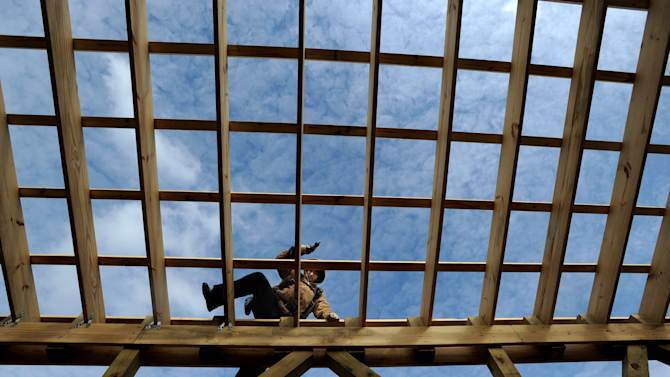 In this Jan. 24, 2013 photo, Rod Cimino of Cookeville, Tenn., works on the rafters of the Owensboro Public Works building in Portland, Tenn. The Commerce Department says construction spending in the U.S. fell 2.1 percent in January compared with December, the largest drop in 18 months. (AP Photo/The Messenger-Inquirer, John Dunham)