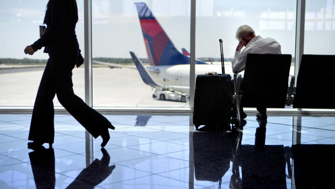 A passenger sits at right in the international terminal at Hartsfield-Jackson airport, Friday, April 26, 2013, in Atlanta. Congress easily approved legislation Friday ending furloughs of air traffic controllers that have delayed hundreds of flights daily, infuriating travelers and causing political headaches for lawmakers.(AP Photo/David Goldman)