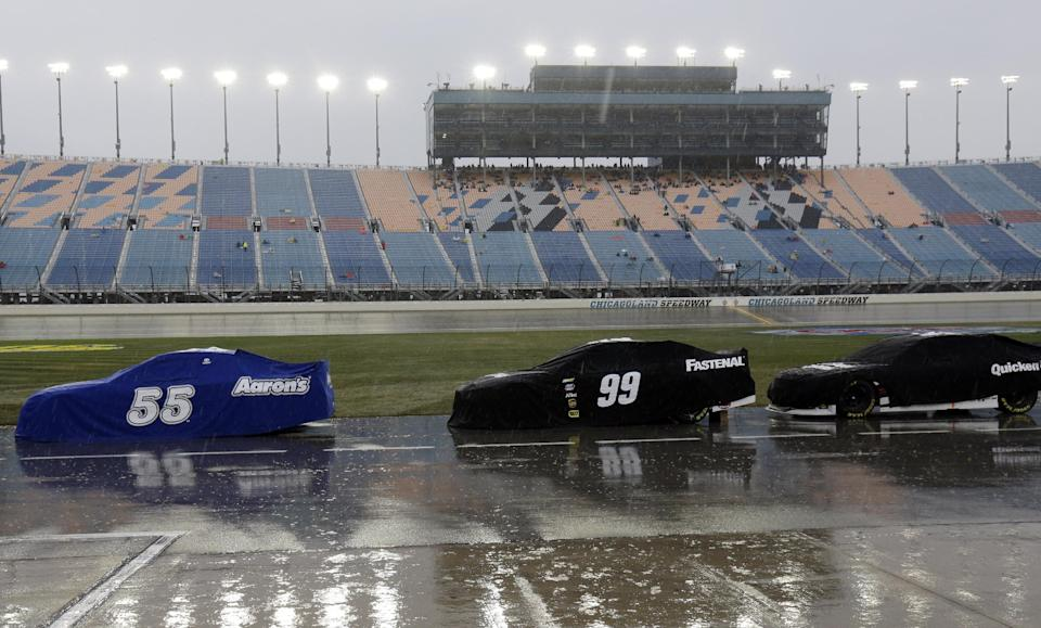 Covered Sprint Cup Series race cars are parked on pit road during rain delay in the NASCAR Sprint Cup series auto race at Chicagoland Speedway in Joliet, Ill., Sunday, Sept. 15, 2013. (AP Photo/Nam Y. Huh)