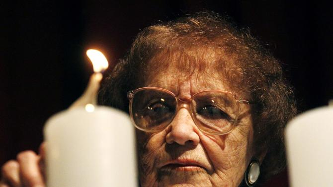 Auschwitz's survivor Lea Novera lights a candle while attending a ceremony during the International Holocaust Remembrance Day at the AMIA Jewish cultural centre in Buenos Aires