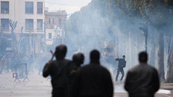 A demonstrator faces riot police officers after the killing of Chokri Belaid in Tunis, Wednesday, Feb. 6, 2013. The Tunisian opposition leader critical of the Islamist-led government and violence by radical Muslims was shot to death Wednesday — the first political assassination in post-revolutionary Tunisia. The killing is likely to heighten tensions in the North African nation whose path from dictatorship to democracy so far has been seen as a model for the Arab world. (AP Photo/Amine Landoulsi)