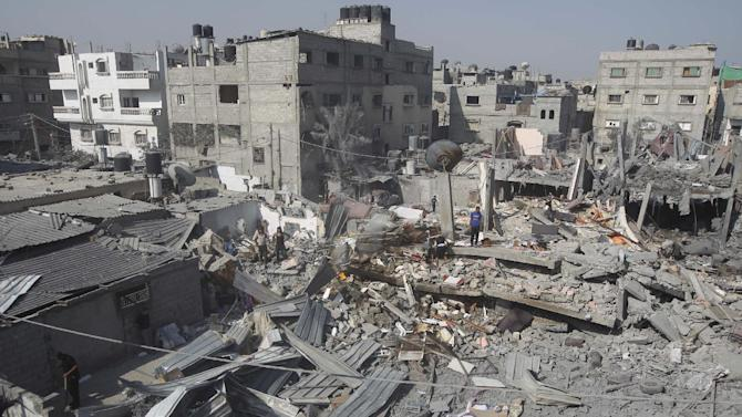 Palestinians inspect the wreckage of a building which was destroyed by an Israeli strike on the southern Gaza city of Rafah, on August 2, 2014