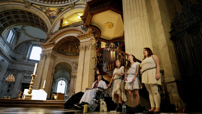 Four women activists of the Occupy movement protest chained to the pulpit inside St Paul's Cathedral as preparations for evensong take place in London, Sunday, Oct. 14, 2012. Several supporters of the anti-corporate Occupy movement chained themselves to the pulpit of St. Paul's Cathedral during a service on Sunday in an action marking the anniversary of its now-dismantled protest camp outside the London landmark.  (AP Photo/Alastair Grant)