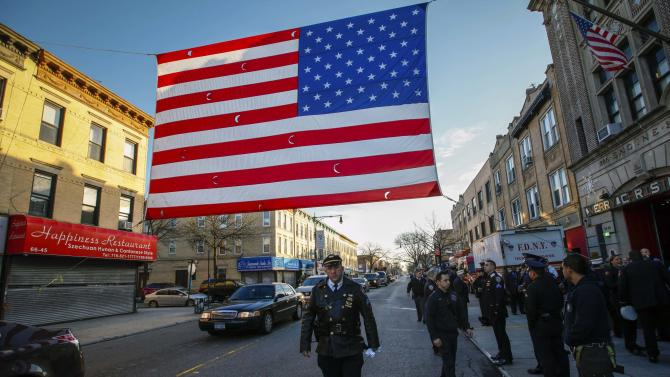 A police officer walks past an U.S. flag hanging over a street near the Christ Tabernacle Church, where the funeral services for NYPD officer Ramos will be held in the Queens borough of New York