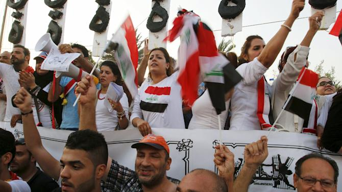 Iraqi people shout slogans during a demonstration against the poor quality of basic services, and power outages and calling for trial corrupt politicians in Baghdad