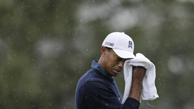Tiger Woods wipes rainwater off his hat as he waits to putt on the ninth hole of the north course at Torrey Pines Golf Course during the second round of the Farmers Insurance Open golf tournament Friday, Jan. 25, 2013, in San Diego. (AP Photo/Gregory Bull)
