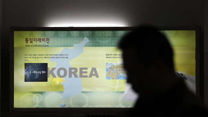 A man passes by a map of the Korean peninsula at the Unification Observation Post near the demilitarized zone between the two Koreas in Paju, north of Seoul, South Korea, Thursday, March 28, 2013. A day after shutting down a key military hotline, Pyongyang instead used indirect communications with Seoul to allow South Koreans to cross the heavily armed border and work at a factory complex that is the last major symbol of inter-Korean cooperation. (AP Photo/Lee Jin-man)