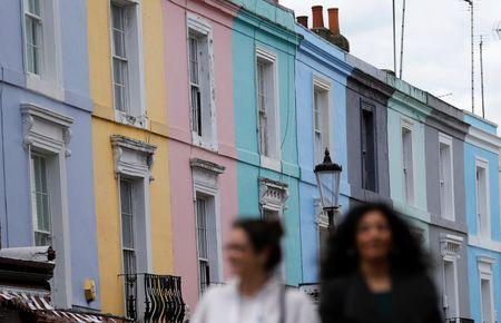Pedestrians walk past a row of houses in London