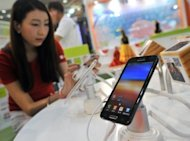 A South Korean woman inspects Samsung's smartphone 'Galaxy Note' during an IT show in Seoul, in May. A US appeals court gave Samsung a temporary reprieve on the sale of its Galaxy Nexus 7 smartphones while leaving intact a court ban on US sales of its tablet computers in a patent battle with Apple