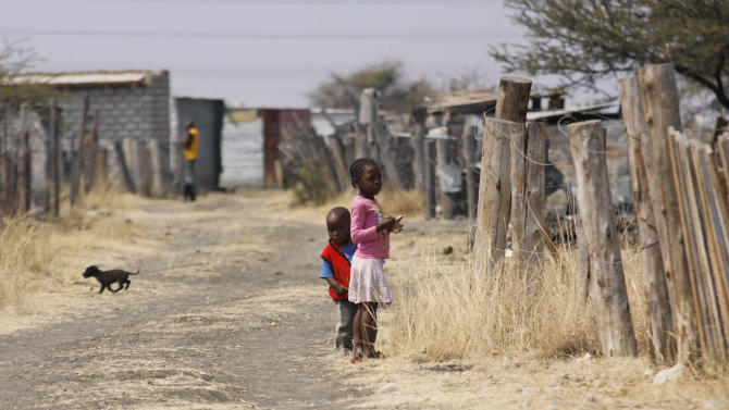 FILE In this photo taken Tuesday, Aug. 28, 2012 children walk among miners shacks in the Wonderkop settlement next to the Lonmin Platinum Mine near Rustenburg, South Africa. The current unrest in the mining industry started in August with the miners staging a wildcat strike that led to a violent confrontation in which police shot and killed 34. More than 70 others were wounded in the worst case of of state-led violence since the end of apartheid. (AP Photo-File)