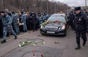 People throw flowers on a road in Moscow on March 3,…