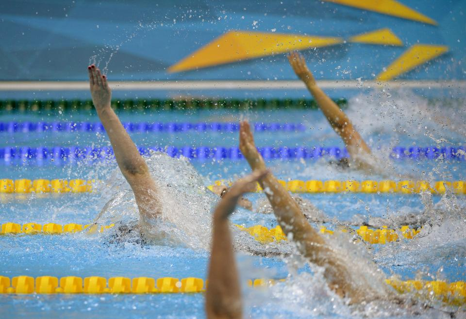 United States' Missy Franklin, left, leads in the women's 100-meter backstroke swimming final at the Aquatics Centre in the Olympic Park during the 2012 Summer Olympics in London, Monday, July 30, 2012. (AP Photo/Mark J. Terrill)