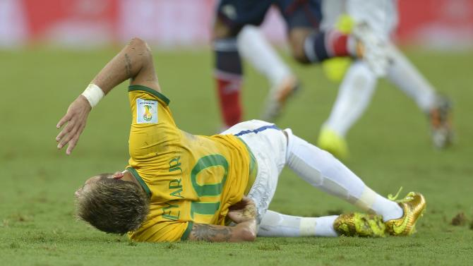 Brazil's Neymar holds his back after being fouled during the World Cup quarterfinal soccer match between Brazil and Colombia at the Arena Castelao in Fortaleza, Brazil, Friday, July 4, 2014. (AP Photo/Manu Fernandez)