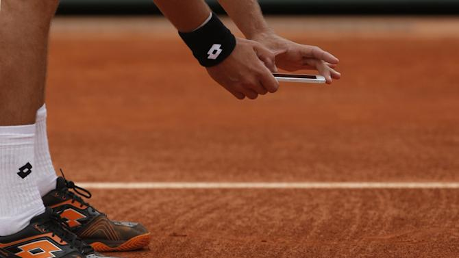 Ukraine's Sergiy Stakhovsky takes a picture with his smart phone after contesting the decision of the umpire to call the ball in, in his first round match against Richard Gasquet of France at the French Open tennis tournament, in Roland Garros stadium in Paris, Monday, May 27, 2013. (AP Photo/Michel Spingler)