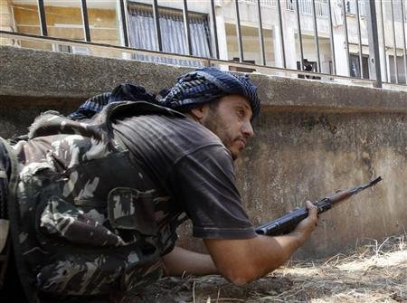 A Free Syrian Army fighter takes up position during clashes in Aleppo