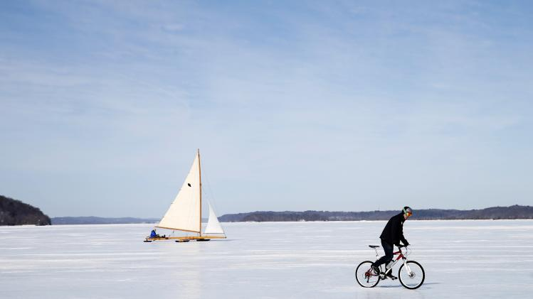 An antique ice boat sails behind a cyclist across the frozen Hudson River near, Astor Point in Barrytown, New York