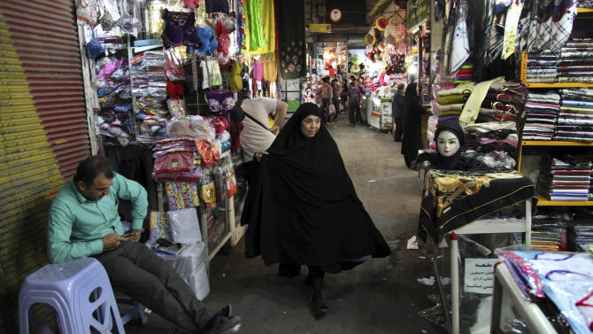 A woman makes her way through the old bazaar, in Tehran Iran, on Sunday, May 12, 2013. Former President Akbar Hashemi Rafsanjani's made a last minute surprise decision on Saturday to enter Iran's presidential election process, which now includes more than 680 hopefuls and will culminate June 14 with just a handful of names on the ballot to succeed Mahmoud Ahmadinejad. In one of his first statements since joining the race, Rafsanjani spoke in general terms Sunday of seeking a new ``economic and political'' rebirth in a time of ``foreign threats and sanctions.'' (AP Photo/Vahid Salemi)