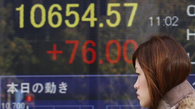 A woman walks by an electronic stock board of a securities firm in Tokyo, Thursday, Jan. 10, 2013. A positive start to U.S. corporate earnings season helped boost Asian stock markets Thursday. (AP Photo/Koji Sasahara)