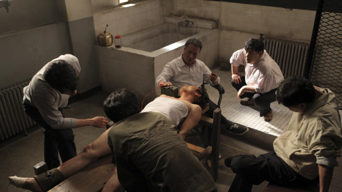 "In this undated photo released on Friday, Oct. 5, 2012 by Busan International Film Festival, South Korean actor Lee Kyeong-yeong, third from right on a chair, acts as a torturer in a scene from the film ""National Security."" The film based on the memoir of a democracy activist who was tortured in the 1980s by South Korea's military rulers is provoking discussion about the country's not-so-distant authoritative past and the influence it will have on this year's presidential election. (AP Photo/Busan International Film Festival) EDITORIAL USE ONLY"