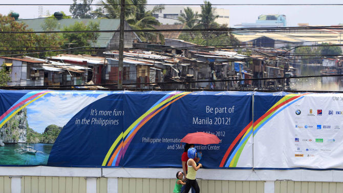 Residents walk past a wall covered with a tarpaulin poster of the ongoing 45th Annual Board of Governors meeting of the Asian Development Bank at suburban Pasay city south of Manila, Philippines, Thursday May 3, 2012. Delegates attending the international conference of the ADB in the Philippines capital may not see what they came to discuss: abject poverty. The makeshift, temporary wall on both sides of the bridge from the airport to downtown Manila, hides a sprawling slum along a garbage-strewn creek in the background. (AP Photo/Bullit Marquez)