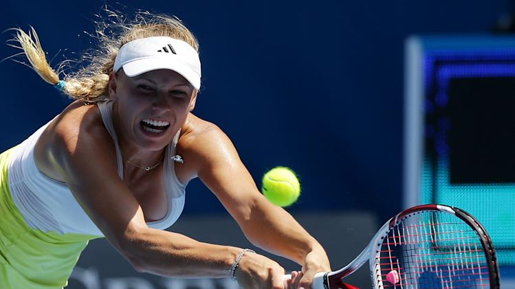 Denmark's Caroline Wozniacki hits a backhand return to Russia's Svetlana Kuznetsova during their fourth round match at the Australian Open tennis championship in Melbourne, Australia, Monday, Jan. 21, 2013. (AP Photo/Aaron Favila)