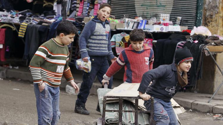 Children play along a street in Aleppo's Bustan al-Qasr neighbourhood