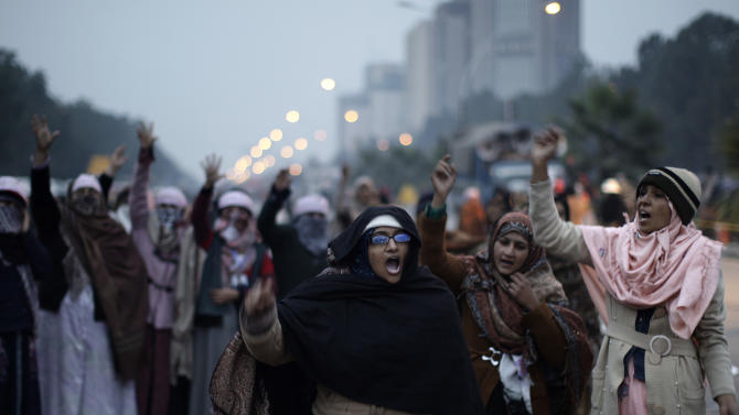 Supporters of Pakistani Sunni Muslim cleric Tahir-ul-Qadri, chant slogans, while camping out near the parliament, during an anti-government rally in Islamabad, Pakistan, Thursday, Jan. 17, 2013. Several thousand protesters shouting anti-military slogans displayed the bodies of 15 local villagers in northwestern Pakistan, claiming they were shot dead in their homes by security forces in an overnight raid. Hours later, police dispersed the protesters using water cannons and tear gas. (AP Photo/Muhammed Muheisen)