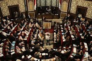 Members of Syria&#39;s newly-elected parliament hold their first official sesssion in Damascus. A deeply divided opposition has failed the Syrian people, its outgoing leader charged on Thursday, as a new parliament again dominated by the ruling Baath party held its first session in Damascus