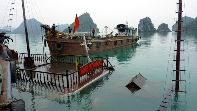 FILE - In this Feb. 18, 2011 file photo, a tour boat, submerged in the water, is pulled up in the Halong Bay in northern Quang Ninh province, Vietnam, a day after 12 people from nine nations died when their boat sank early in the morning. Each day, up to 10,000 tourists from around the world sail around the bay, a UNESCO-heritage site and one of the country's most visited tourist attractions, and gaze at its stunning limestone pillars and caves. But at least four deadly accidents over the last 10 years and many more alarming safety incidents recounted on traveler's blogs have led to allegations that the ships are cutting corners. (AP Photo/Dinh Tran Trung Hau, File)