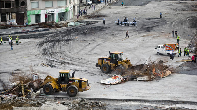 Bulldozers clear construction materials used by protesters to make barricades in Taksim square, in Istanbul, Turkey, June 16, 2013. Turkish riot police firing tear gas and water cannon took less than half an hour on Saturday to bring to an end an 18-day occupation of an Istanbul park at the center of the strongest challenge to Prime Minister Recep Tayyip Erdogan's 10-year tenure. (AP Photo/Vadim Ghirda)