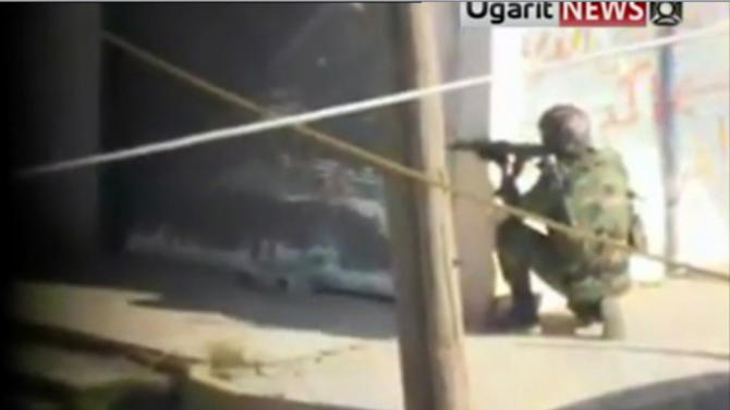 In this image from amateur video made available by the Ugarit News group on Friday, Dec. 2, 2011, a soldier takes aim in Homs, Syria. The United Nations' human rights chief called on the international community to protect Syrian civilians Friday as violence surged across the country, with hours of intense shooting that sent stray bullets whizzing across the border.(AP Photo/Ugarit News Group via APTN) THE ASSOCIATED PRESS CANNOT INDEPENDENTLY VERIFY THE CONTENT, DATE, LOCATION OR AUTHENTICITY OF THIS MATERIAL.  TV OUT